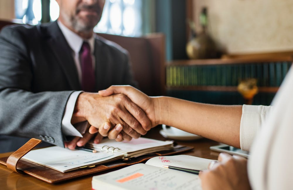 Conveyancing lawyer in Campbelltown and client handshaking